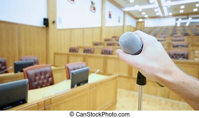Microphone in hall and hand which holds its close up -...