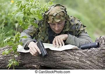Military Camouflaged man in forest with black handgun, map...