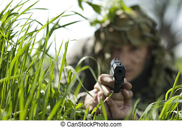 gunpoint - Military Camouflaged man in forest with black...