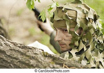 Camouflaged military man - Young Camouflaged military man in...