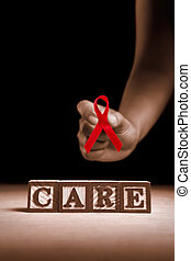 AIDS care - Word Care from wooden block with hand holding...