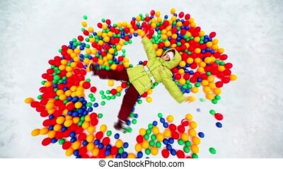 Little girl lying in pile of colored balls in snow hollow,...