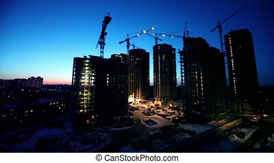 Night shift at construction site in foreground of dormitory area cityscape