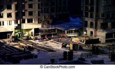 Labourers work at construction site on winter night, closeup...