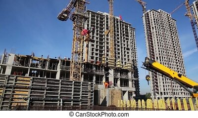 tall buildings under construction and cranes