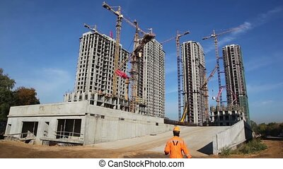 tall buildings under construction with cranes against sky -...