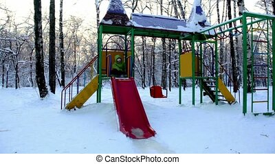 Girl sits on construction at childrens playground and slide down, in winter day