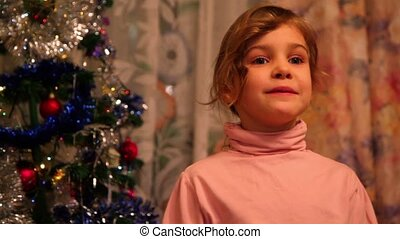 Girl stand near decorated christmas tree and says her...