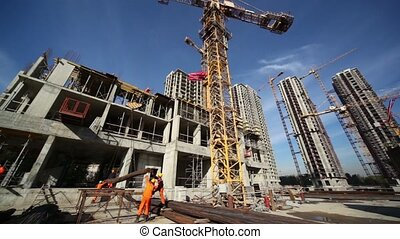 Workers lift the valve using a high crane on construction...
