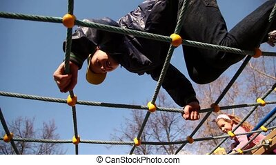 Kids climb on rope lattice at playground, closeup view from below