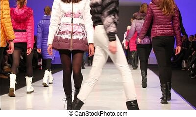 Young models walk away in winter clothes from Snowimage...