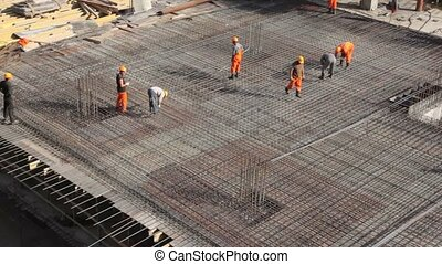 workers constructing metal frame on building place - Few...