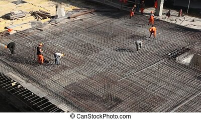 workers constructing metal frame on building site - Several...