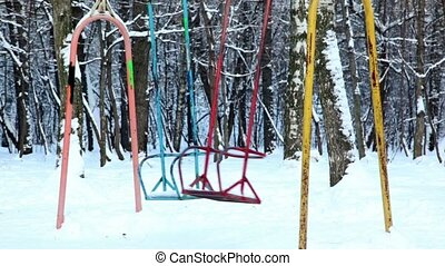 Two empty metallic swing sway in park at winter day