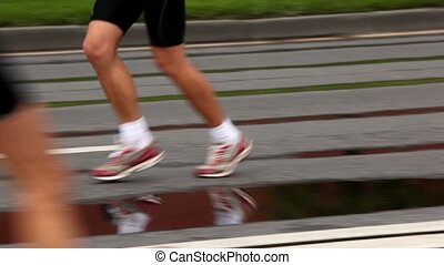 Man naked legs run in jogging shoes on asphalt with puddles,...