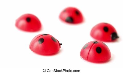 Five toy ladybugs lay in ring, composition rotates