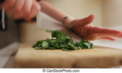 Chopping Coriander - Chopping fresh coriander cilantro on a...