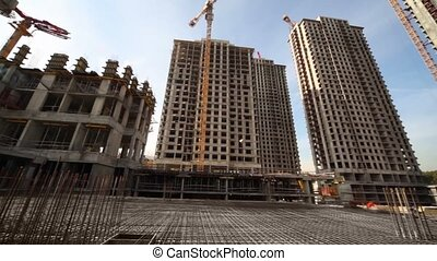 Carcass in between unfinished tall buildings and cranes -...
