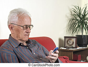 Real people - Elderly man looking at a mobile phone