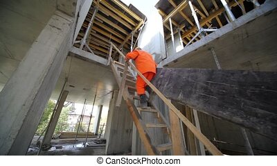 workers carry huge plate by stairs to second storey - Two...
