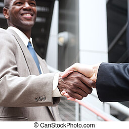 closeup of African American businessman shaking hands with...