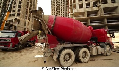 Concrete mixer stand at building place, truck full of sand arrives