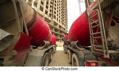 concrete mixer stand near unfinished buildings - Two...