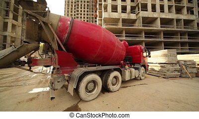 Concrete mixer stand near unfinished building, upward camera...