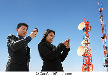 Asian business people texting and antenna - Asian business...