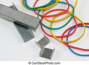 Stationery Supplies - Elastic bands and staples on white.