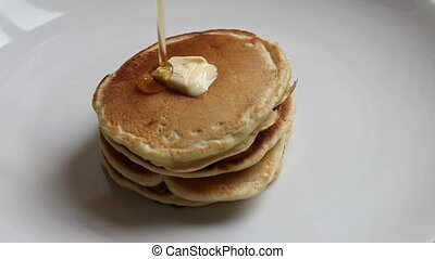 Pouring maple syrup on pancakes - Pouring maple syrup on...