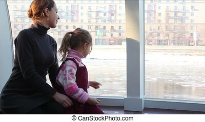 Mother and daughter sit inside ship floating down river in...