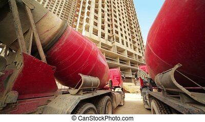 Between two concrete mixer near unfinished house - Between...