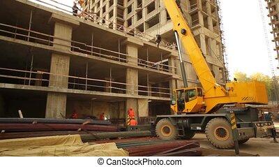 Crane rises hook, worker weld inside unfinished building