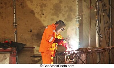 Worker weld metal gratings by acetylene torch