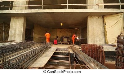 Two workers weld metal gratings by acetylene torches - Two...