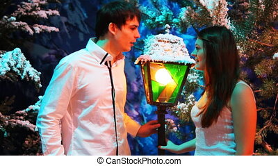 couple stands and talk near colored lantern in winter woods...