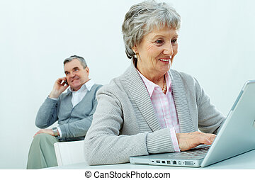 Busy seniors - Portrait of senior woman typing with a man...