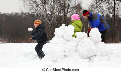 mother and father with children play snowballs behind...
