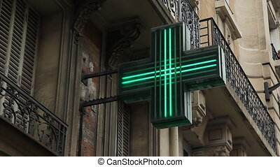 Paris Pharmacy sign. - Green flashing neon sign indicates...