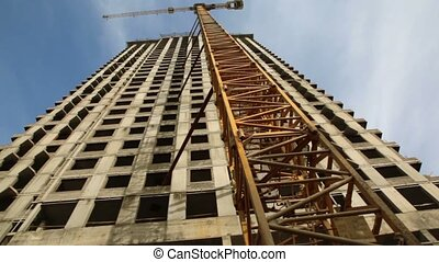 Crane stand near unfinished building at construction site -...