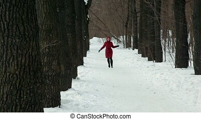 Man catches up with woman among trees at park alley at...