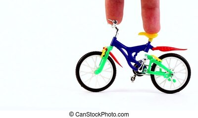 Fingers ride on toy bike, then other fingers came on...