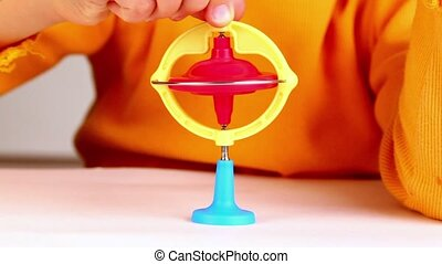 Little girl sets spinning top which starts to rotate, which...