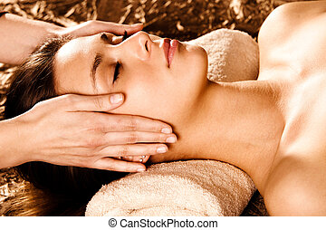 face massage - woman enjoy in face massage in spa salon
