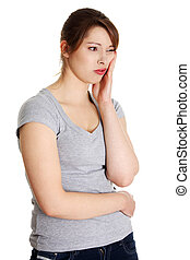 Tooth ache - Young woman pressing her bruised cheek with a...