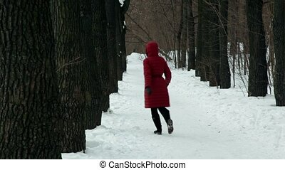 Woman snake walk among trees on park alley at winter day