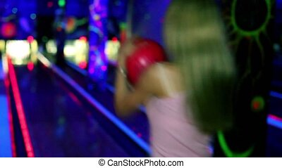 girl stands and smiles with bowling ball and then throws it...