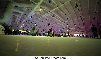 People skate on large indoor ice rink with colored...
