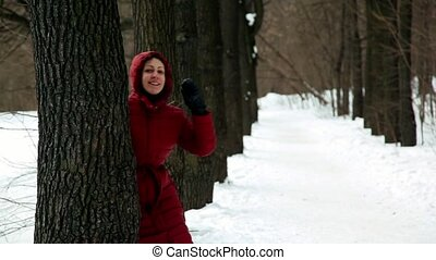 Woman comes out from behind trees and then hide back several...